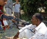 A rebel points his rifle at a man accused of being a mercenary fighting for Muammar Gaddafi, inside a fire station in Tripoli August 26, 2011. Libyan rebels said they were sending in special forces units in their hunt for fugitive strongman Gaddafi, whose supporters are now pinned down in pockets of resistance in the capital, Tripoli. REUTERS/Goran Tomasevic (LIBYA - Tags: CIVIL UNREST CONFLICT)
